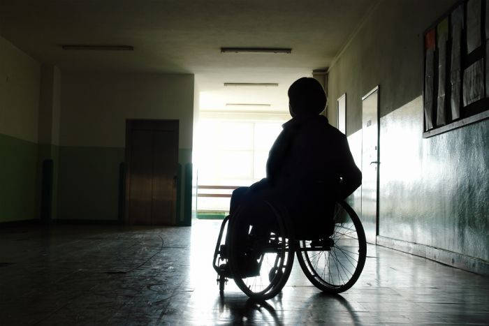 silhouette of female wheelchair user in corridor
