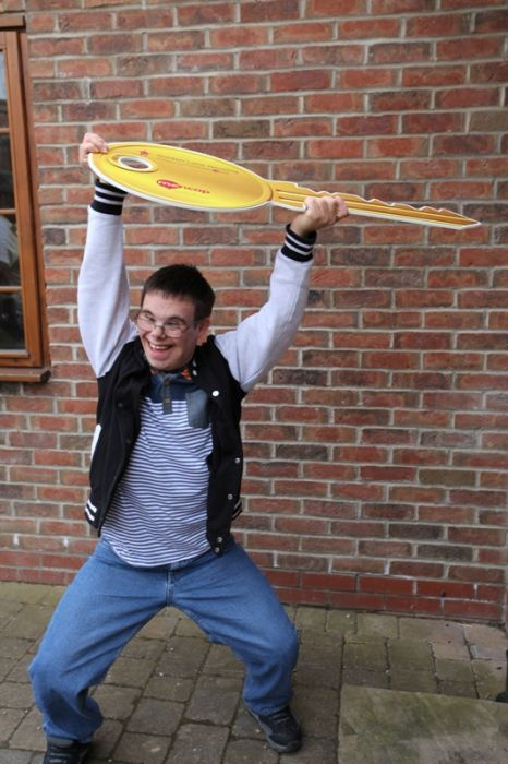 Picture of James Wilkinson with a giant key outside new home © Golden Lane Housing