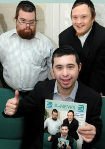 Kisharon service users Meir Halpern (left), Yonaton Lev + Eli Cohen (seated) with a pilot edition of the charity's K-NEWS produced in an Easy Read format.  PHOTO: JOHN RIFKIN