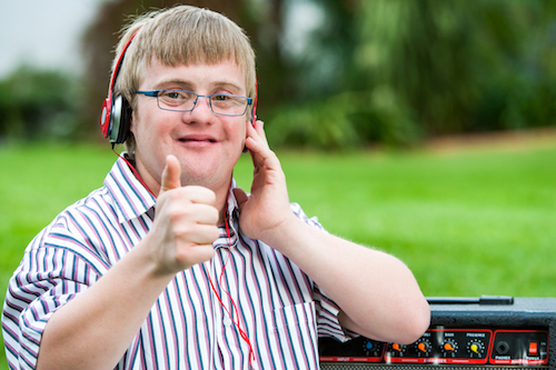 Close up portrait of down syndrome boy with headset doing thumbs up outdoors.