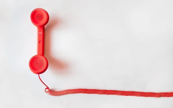 A red phone with a cord lies on a white background