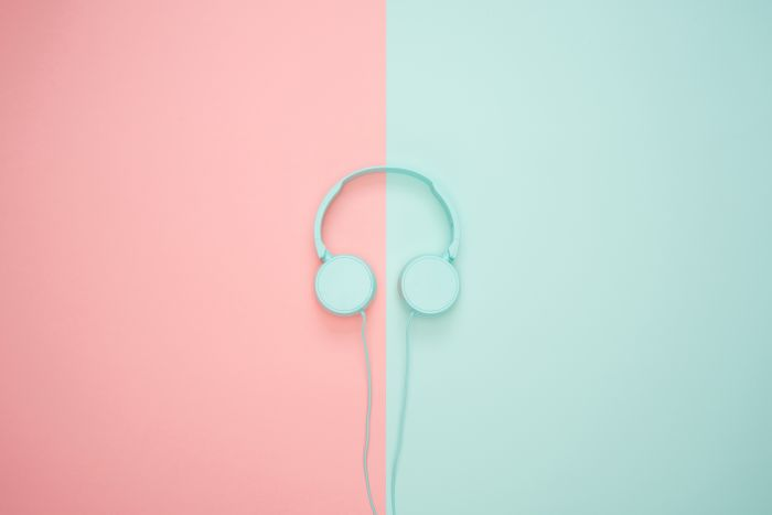 Blue headphones on a pink and blue background