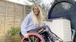 Gem poses in her wheelchair which has pink wheels in her back garden